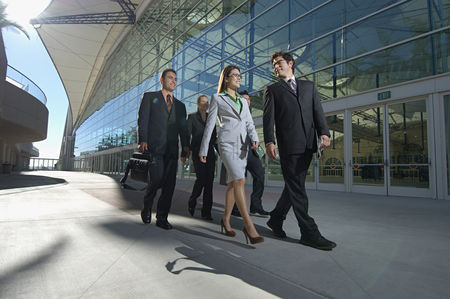 Business suit : Group of business people walking past office building