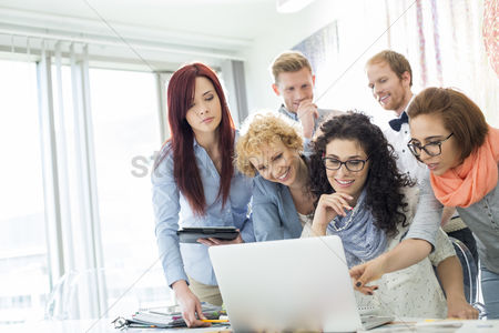 Internet : Group of businesspeople using laptop at desk in creative office