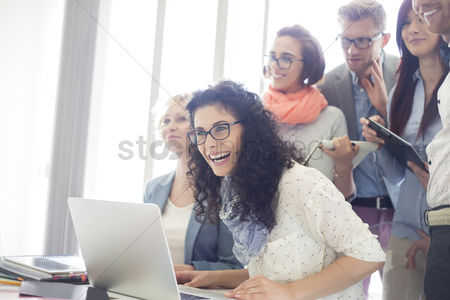 Business women : Group of cheerful businesspeople with laptop at desk in creative office