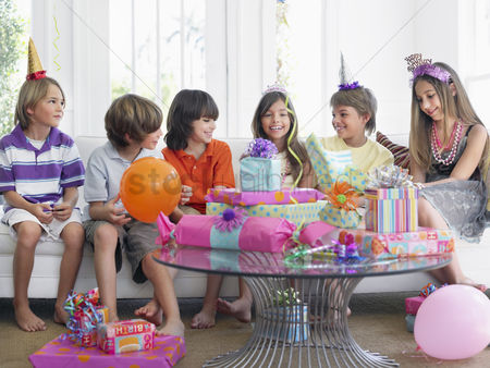 Pre teen : Group of children  7-12  sitting on sofa at birthday party