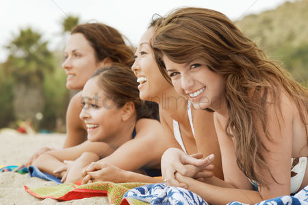 Hispanic : Group of four happy women lying down on the beach