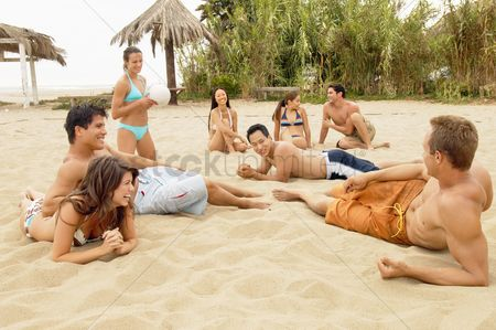 Hispanic : Group of friends talking on the beach