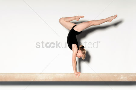 Pre teen : Gymnast  13-15  doing handstand on balance beam side view