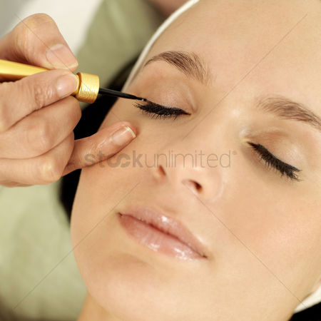 Relaxing : Hand applying liquid eyeliner on woman s eyelid