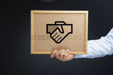 Cork board : Hand holding a cork board with cooperation concept