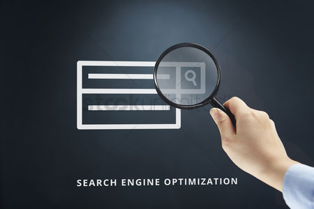 Media : Hand holding a magnifying glass with search engine optimization concept