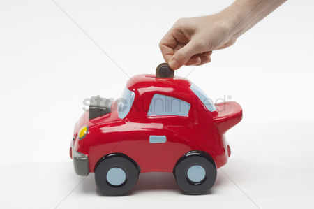 Spending money : Hand putting money in car shaped piggy bank