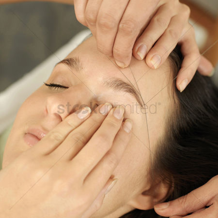 Pain : Hand using thread to remove facial hair from woman s face