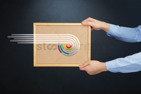 Cork board : Hands holding a board with abstract ring charts