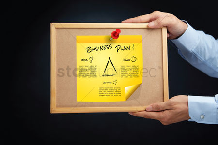 Cork board : Hands holding a board with business plan