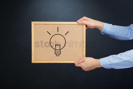Cork board : Hands holding a cork board with business innovation icon