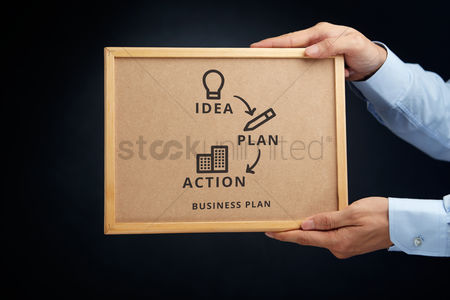 Cork board : Hands holding a cork board with business plan concept