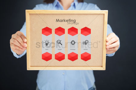 Cork board : Hands holding a cork board with marketing strategy concept