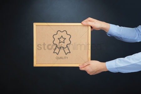 Cork board : Hands holding board with quality concept