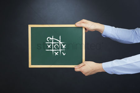 Handdrawn : Hands holding chalkboard with tic tac toe drawing