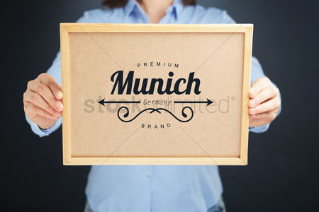 Cork board : Hands holding cork board with munich trademark concept