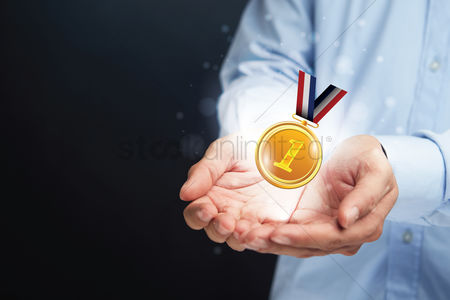 First : Hands presenting a medal
