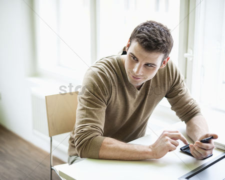 Czech republic : Handsome businessman holding cell phone while looking away in office