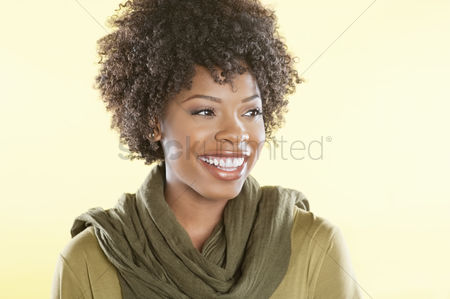 Head shot : Happy african american woman with a stole round her neck looking away over colored background