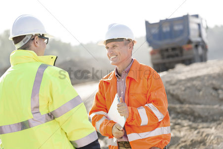 Transportation : Happy engineer discussing with colleague at construction site on sunny day