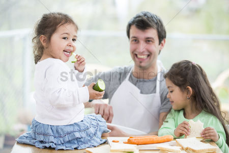 Czech republic : Happy father preparing sandwiches while daughters eating at home