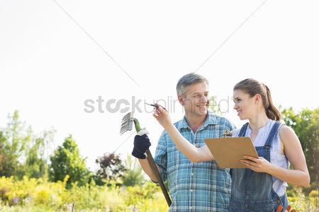 Supervisor : Happy female supervisor explaining something to gardener at plant nursery