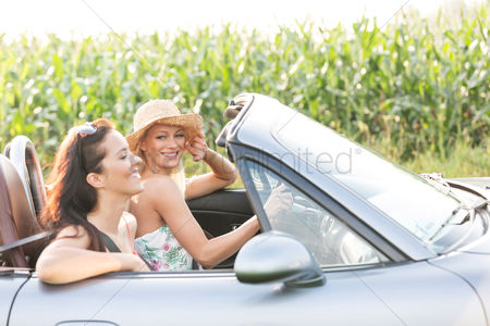 On the road : Happy friends enjoying road trip in convertible