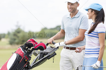 Pushing : Happy friends with bag talking at golf course
