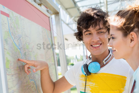 On the road : Happy man showing places on map to woman outdoors
