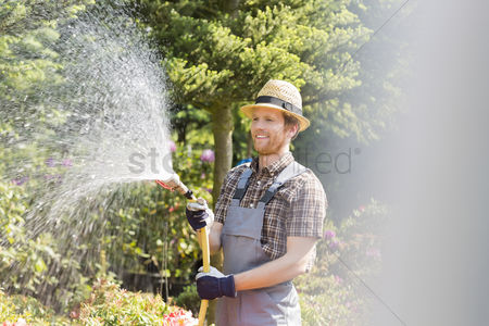 Greenhouse : Happy man watering plants at garden