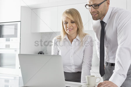 Three quarter length : Happy mid adult business couple using laptop at kitchen counter