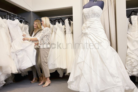 Offspring : Happy mother and daughter shopping together for wedding gown in boutique