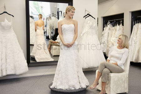 Offspring : Happy mother looking at young daughter dressed in wedding gown in bridal boutique