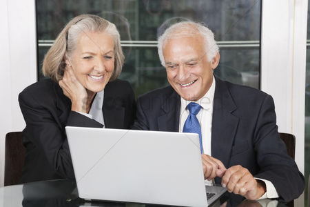 Two people : Happy senior business couple looking at laptop white sitting at table