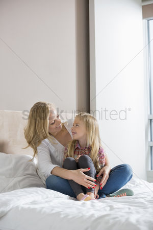 Sitting on lap : Happy woman and daughter looking at each other in bedroom