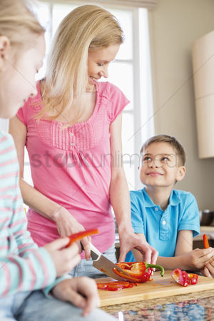 Children : Happy woman chopping red bell pepper while standing with children in kitchen