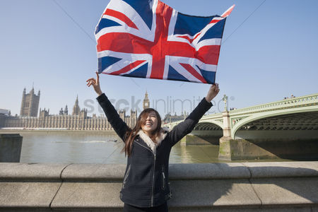 Flag : Happy woman holding british flag while standing against big ben at london  england  uk