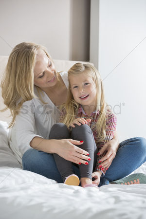 Sitting on lap : Happy woman looking at daughter in bedroom