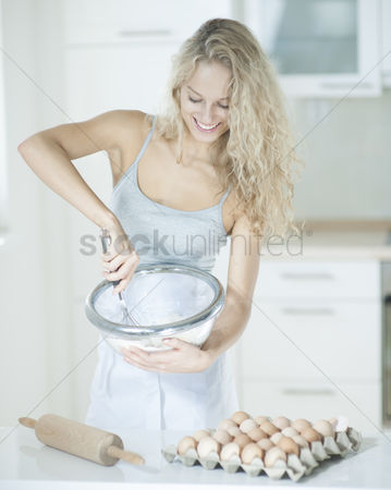Egg tray : Happy woman mixing cookie batter in kitchen at counter