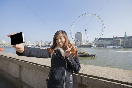 England : Happy woman taking self portrait through cell phone against london eye at london  england  uk