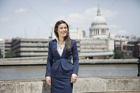 England : Happy young indian businesswoman with st  paul s cathedral in background