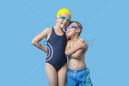 Swimmer : Happy young siblings in swimwear with arm around over blue background