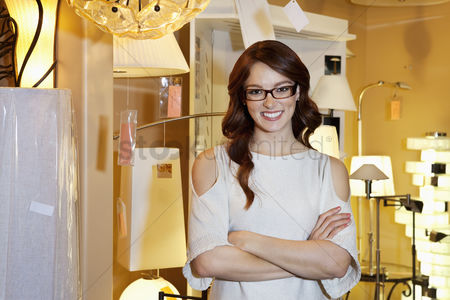 Women : Happy young woman wearing glasses standing with arms crossed in store