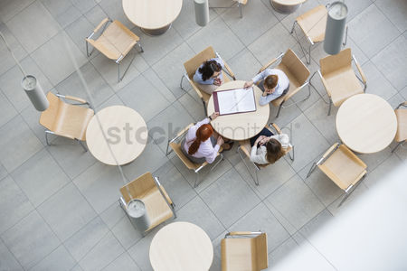 Furniture : High angle view of businesswomen doing paperwork in office canteen