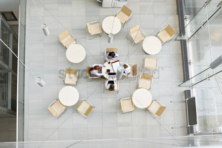 Cell phone : High angle view of businesswomen working in office canteen
