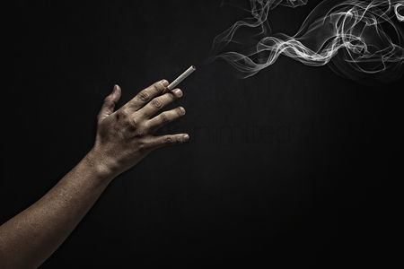 Malaysian chinese : Human hand holding a burning cigarette