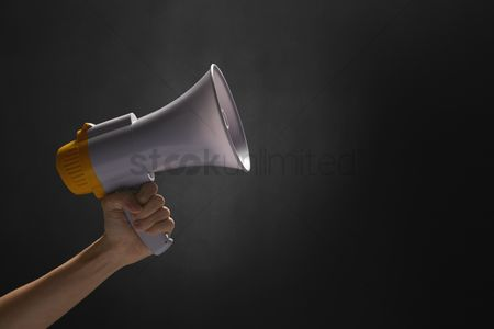 Black background : Human hand holding a megaphone