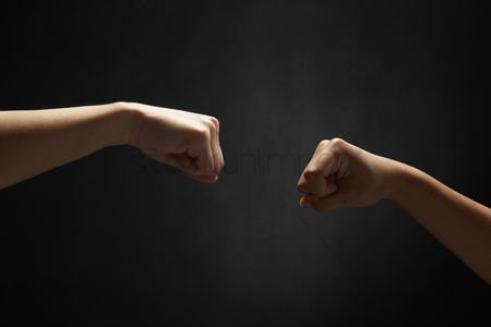 Black background : Human hands doing fist bump