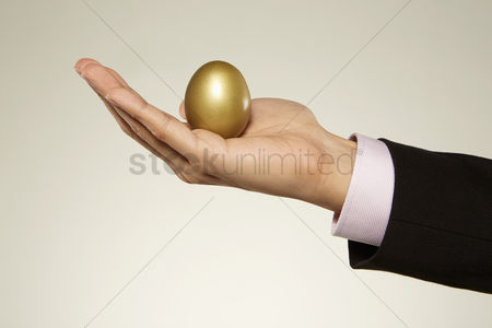 Malaysian chinese : Human holding up a golden egg