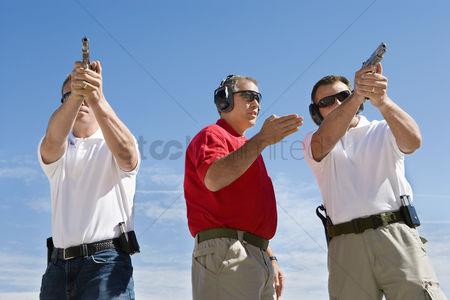 Firing : Instructor assisting men aiming hand guns at firing range